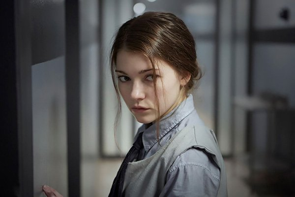 Katie Douglas in the film Level 16. Giving suspicious side eye. Hair tied back, but two loose strands fall over her face; actually appropriate for the character.