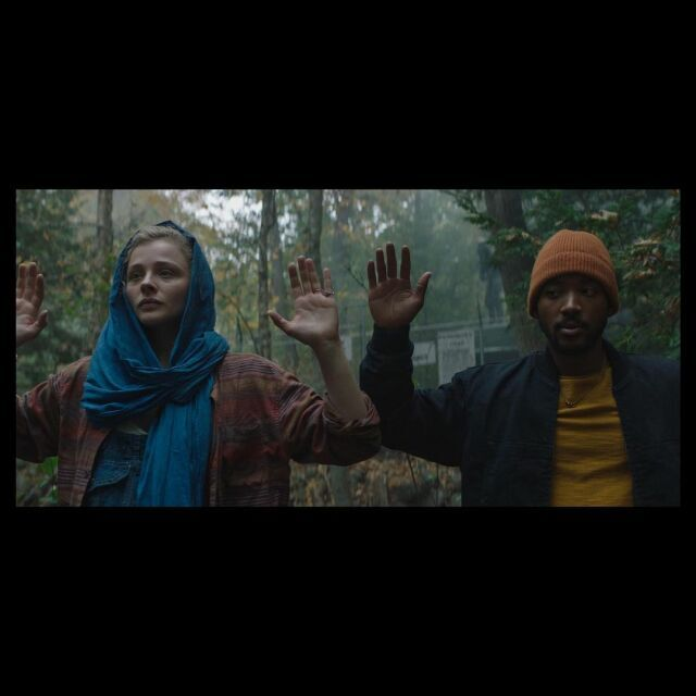 Still from Mother Android. Chloë and co-star in the woods with their hands in the air
