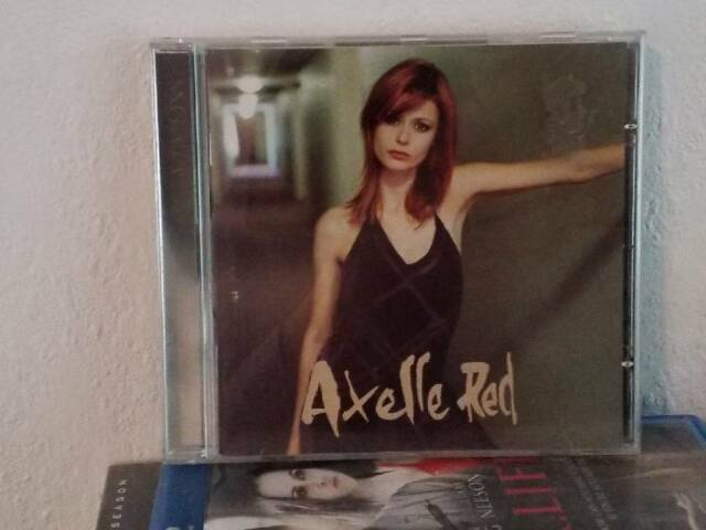Photo of the CD A Tatons with Axelle Red on the cover, in a black dress with her hand leaning against a wall out of frame